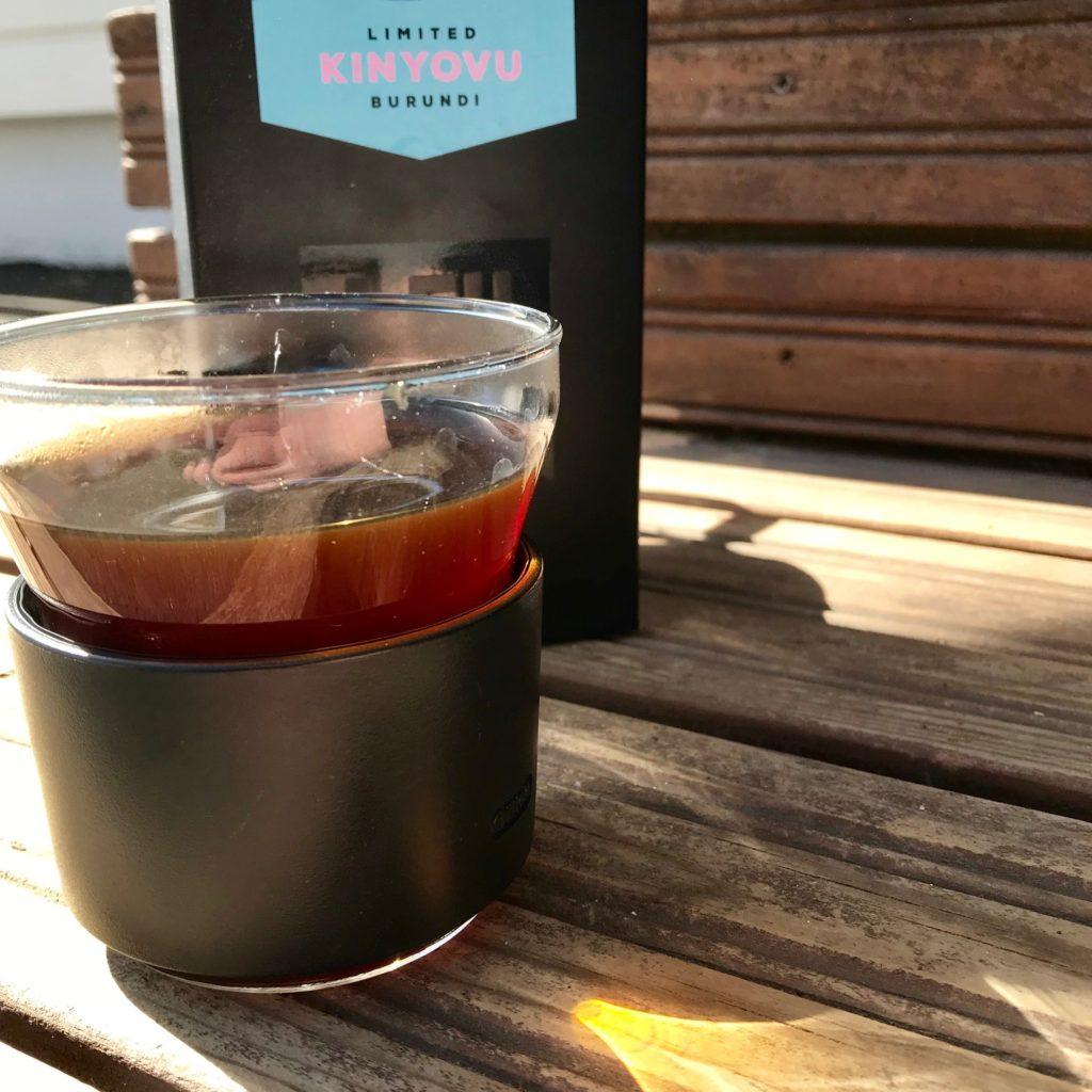 Lehmus Roasteryn burundilaista Kinyovu-kahvia lasissa auringonpaisteessa.