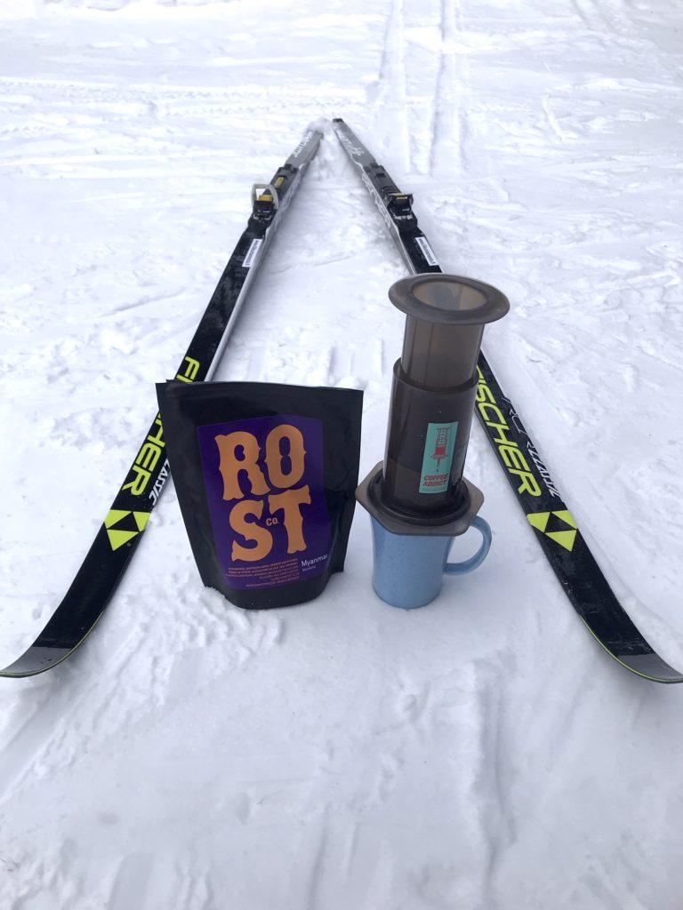 Sukset, kahvipussi, aeropress ja muki lumessa.