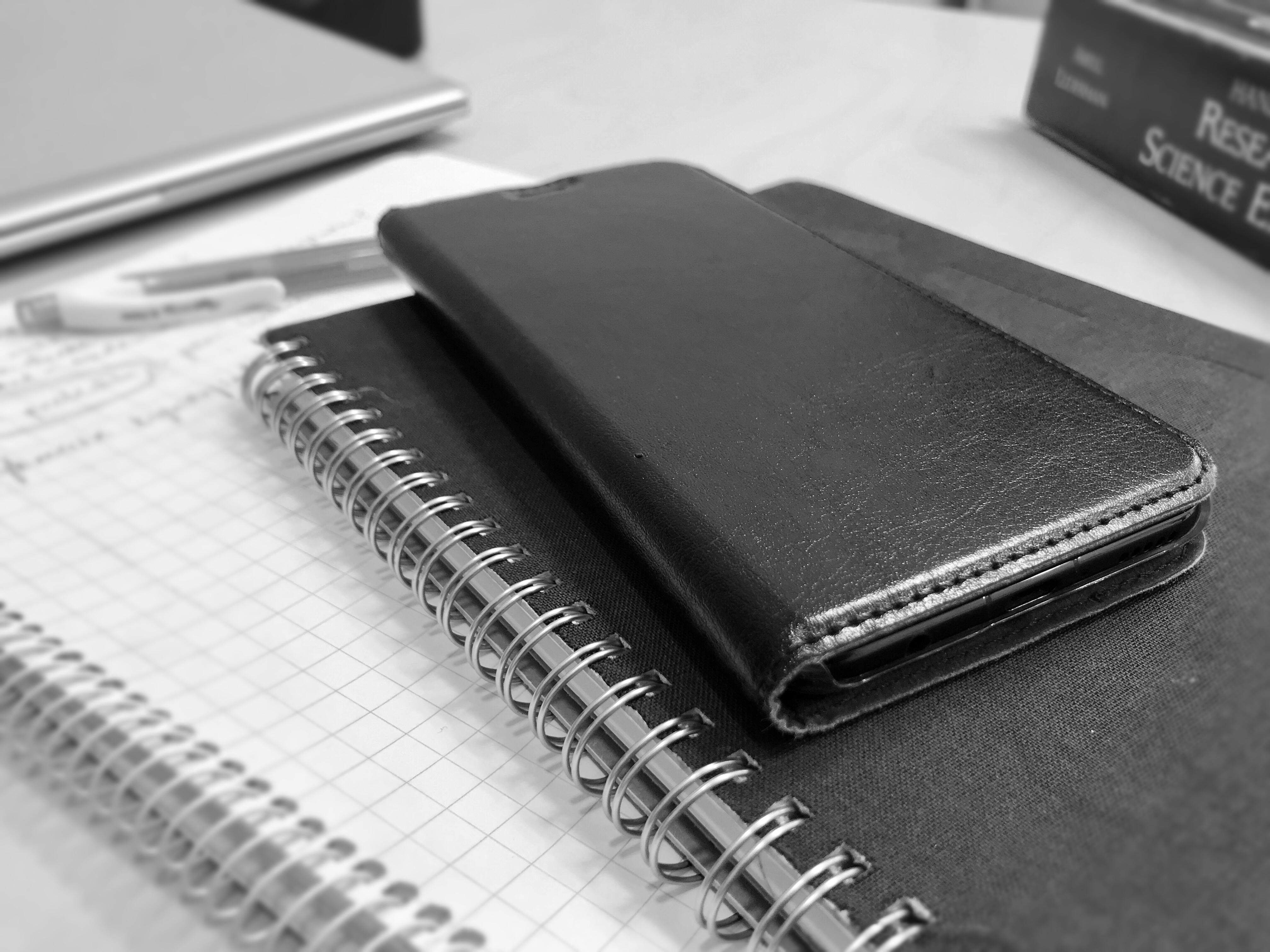 Mustavalkoisessa kuvassa vihko, kalenteri ja kännykkä työpöydällä.