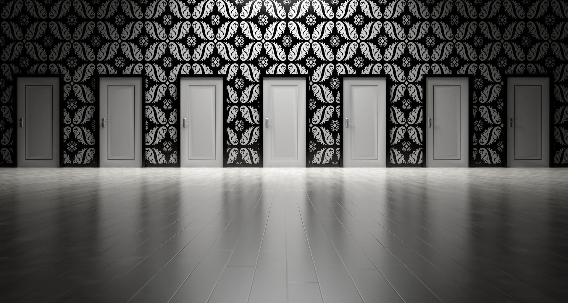 Mustavalkoisessa kuvassa ovien rivistö.
