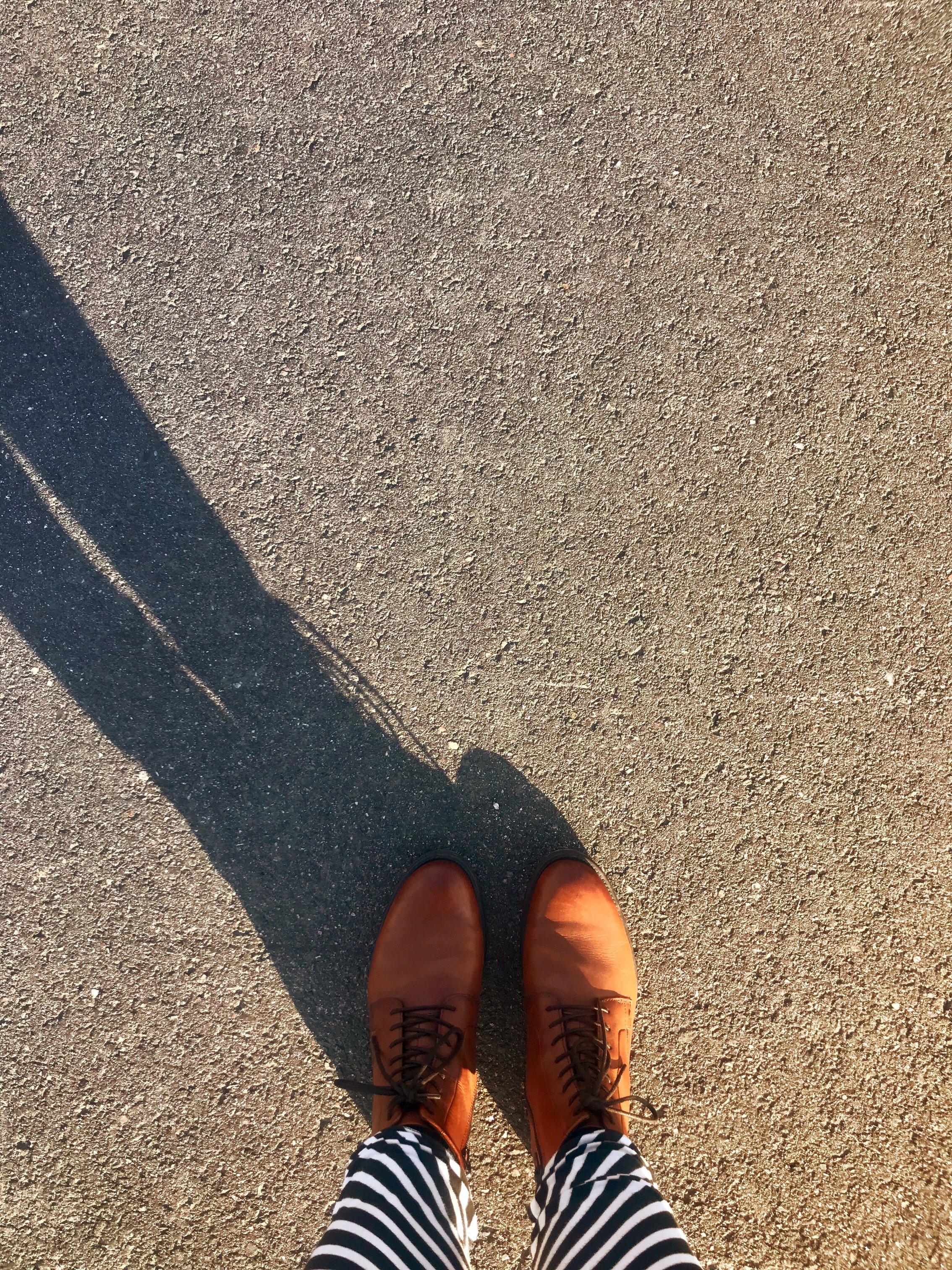 Kuvassa sääret ja ruskeat kengät asvaltilla.