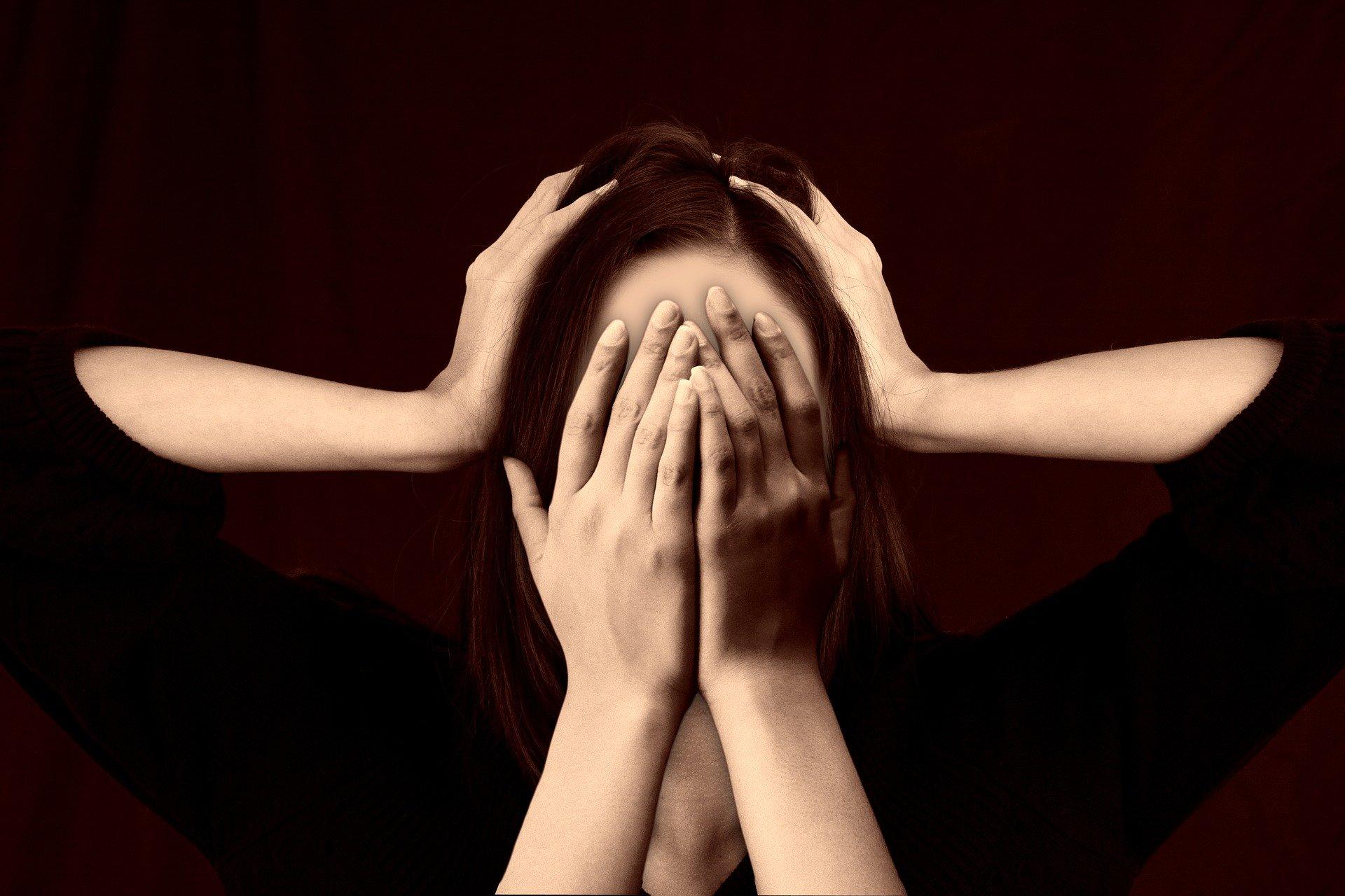 Kuvassa nainen, joka on peittänyt kasvonsa käsillään. Toiset kädet puristavat hänen päätään.