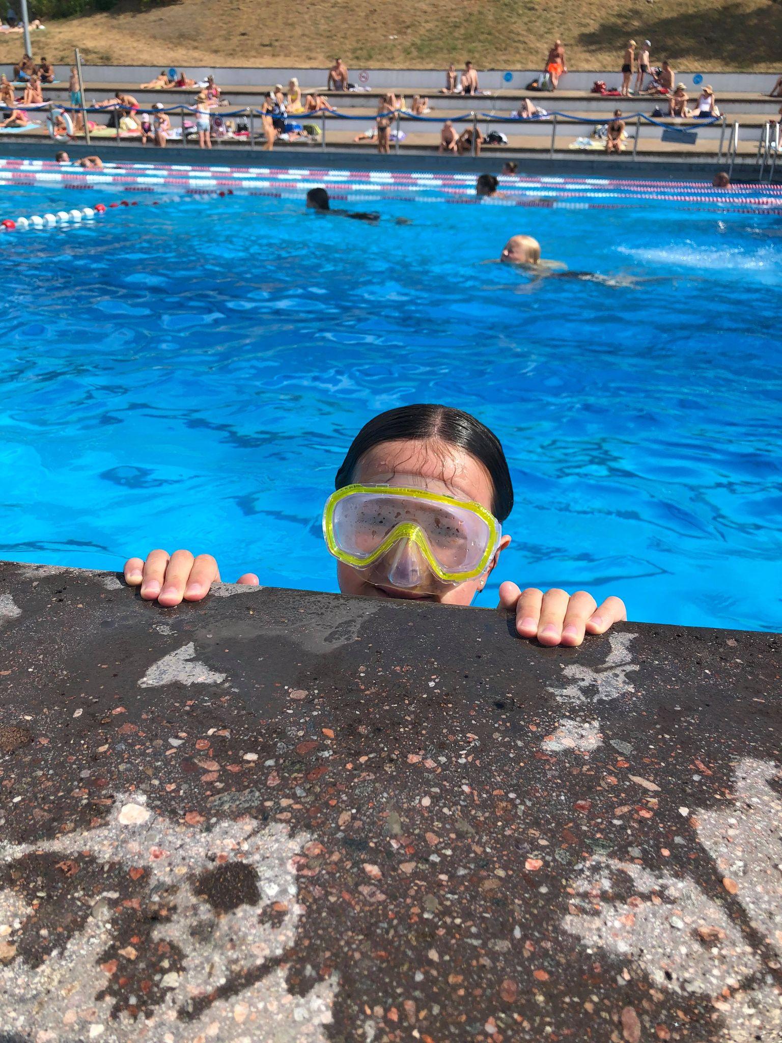 Lapsi kurkkaa uima-altaasta