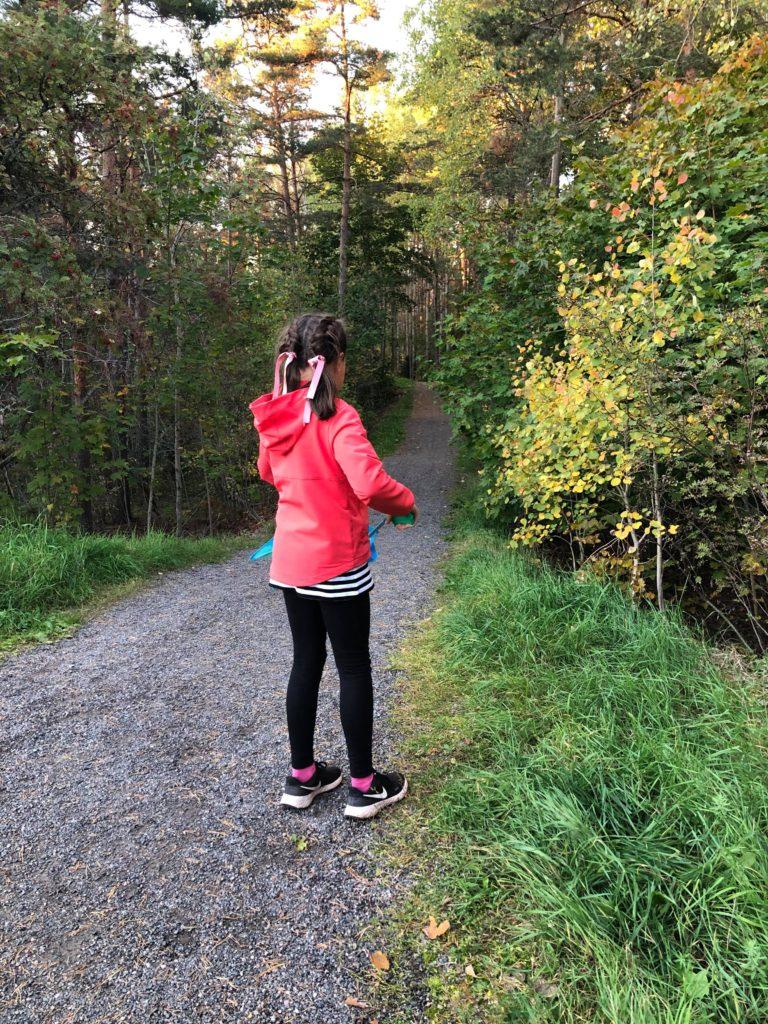 Tyttö kerää roskia metsässä