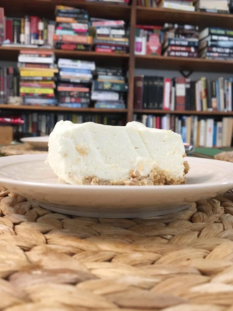 Kuva juustokakun viipaleesta ruokapöydällä, taustalla kirjahylly, koska asumme ahtaasti.